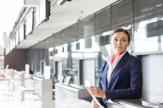Portrait of young attractive passenger agent standing in airport check in area
