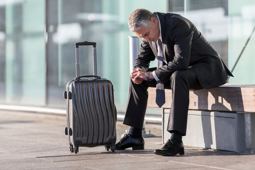 Mature businessman sitting while waiting in the airport