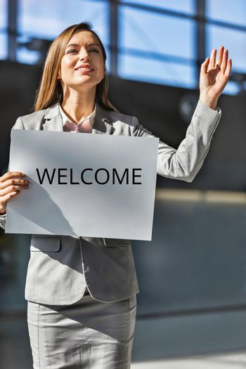 Portrait of young attractive woman standing while holding white board with welcome signage in arrival area at airport