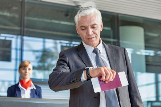 Mature businessman checking time on his watch after checked in at airport