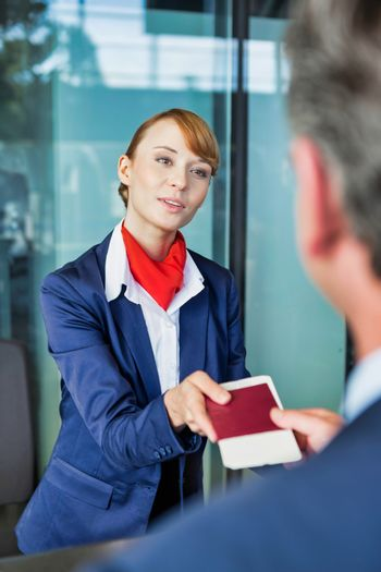 Passenger service agent giving businessman passport and boarding pass in check in area at airport
