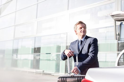 Mature businessman putting his luggage on car trunk