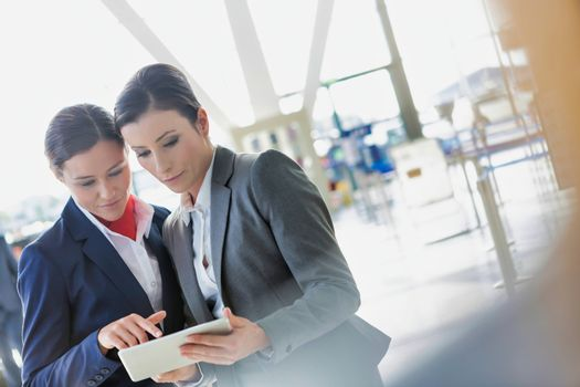 Businesswoman asking for assistance with passenger service agent in airport