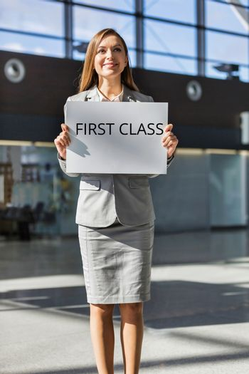 Portrait of attractive woman standing while holding white board with First Class signage for boarding in airport