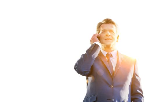 Cutout of mature attractive businessman talking on smartphone