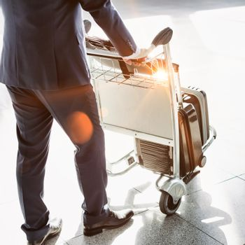Cropped image of businessman pushing baggage cart in airport with lens flare