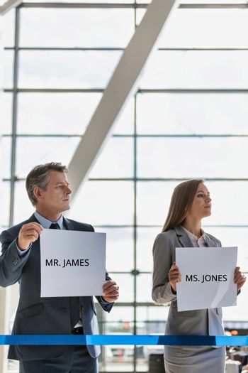 Business people waiting while holding white placard with their boss name in arrival area at airport