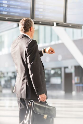 Businessman looking on his watch while waiting for boarding in airport