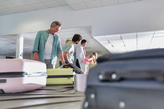 Man getting his suitcase on baggage claiming area in airport