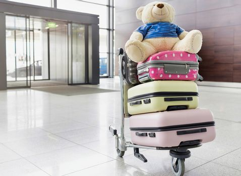 Photo of baggage on cart with teddy bear
