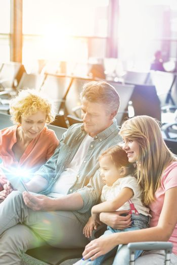 Mature man using digital tablet while his wife and daughter looking in airport