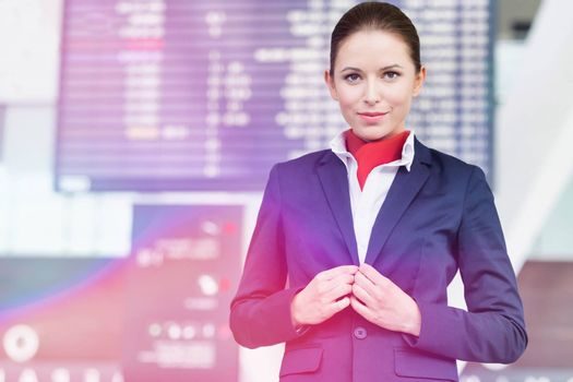 Portrait of young attractive flight attendant standing against f