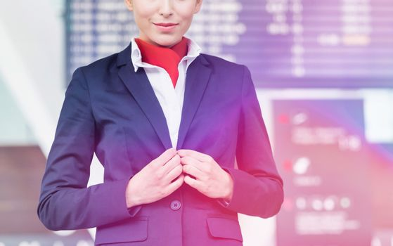 Portrait of young attractive flight attendant standing against flight display monitor in airport