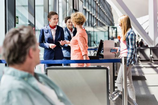 Mature woman on board giving her passport and boarding pass in a