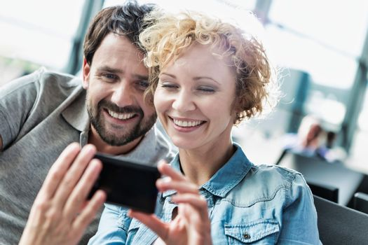 Portrait of mature couple taking and looking at their selfie while waiting for boarding in airport