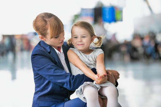 Young attractive airport staff talking to cute little girl in airport