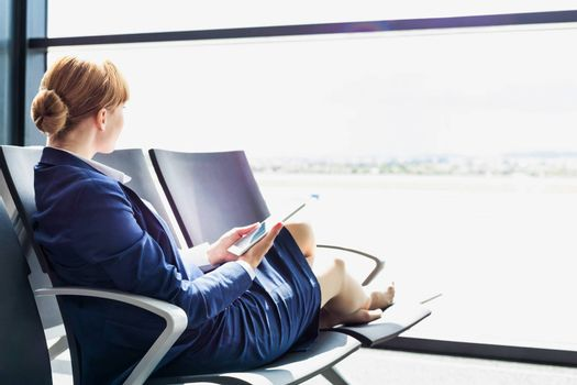 Young beautiful airport staff using digital tablet while sitting on chair during break
