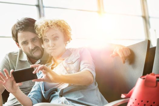 Portrait of mature couple taking selfie while waiting for boarding in airport