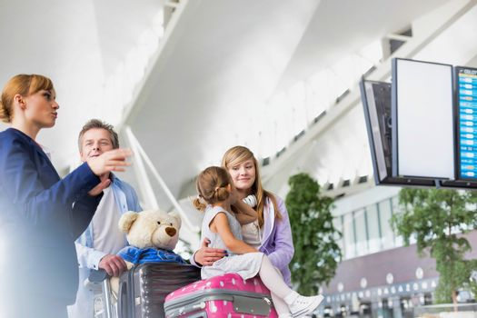 Mature man traveling with two daughters asking for assistance with the airport staff