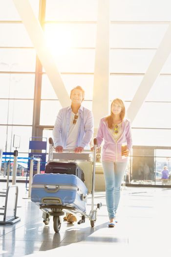 Portrait of man pushing baggage cart for check in with her daugh