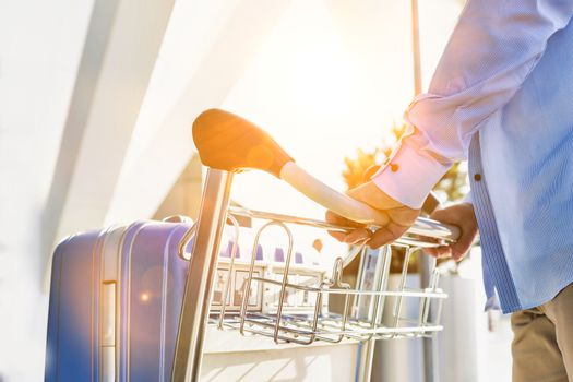 Man pushing cart with his luggage in airport