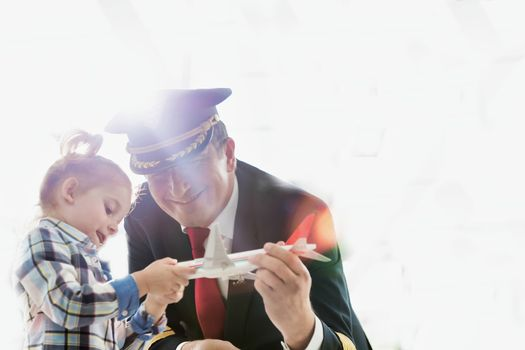 Portrait of mature pilot holding airplane toy while playing with