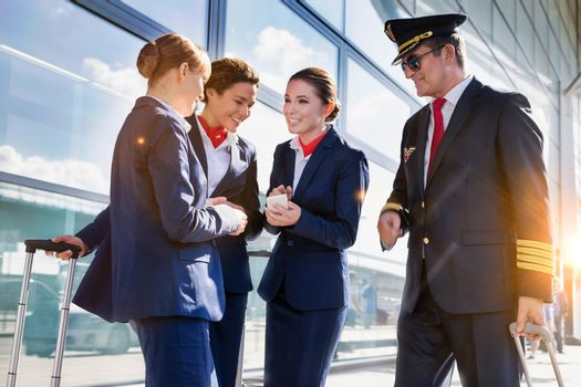 Portrait of mature pilot talking with young attractive flight at