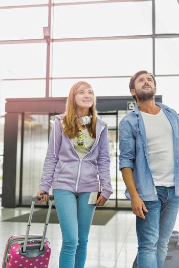 Mature man arriving with his daughter in airport looking for their pick up