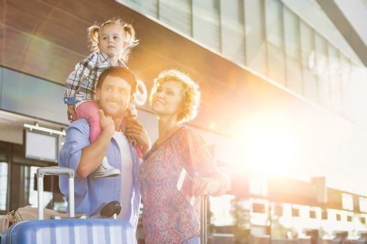 Portrait of one happy family arriving in airport with lens flare