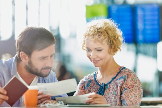 Mature couple looking at their boarding pass in airport