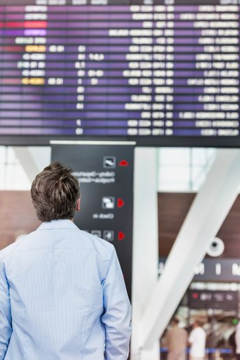 Rear view of mature man looking at his flght on screen in airpor