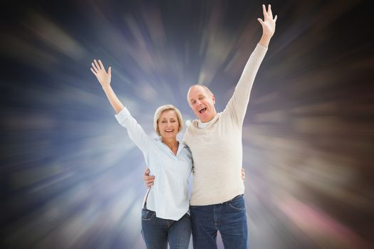 Happy mature couple cheering at camera against dark abstract light spot design