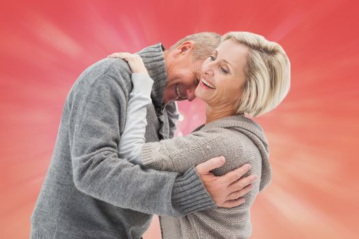 Happy mature couple in winter clothes against red abstract light spot design