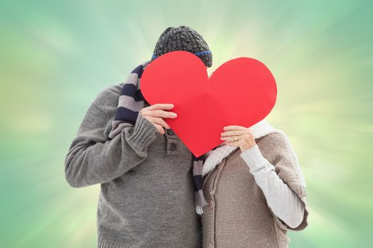 Happy mature couple in winter clothes holding red heart against green abstract light spot design