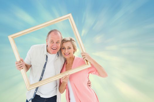 Older couple smiling at camera through picture frame against blue abstract light spot design