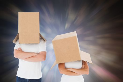 Mature couple wearing boxes over their heads against dark abstract light spot design