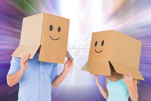 Couple wearing emoticon face boxes on their heads against glittering screen in urban setting