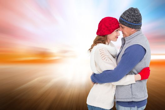 Happy couple in warm clothing hugging against field with light wave