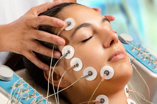 Woman having electrical facial skin tightening treatment.