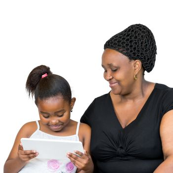 Close up portrait of little african girl with mother isolated on white background.Mother and daughter looking together at digital tablet.