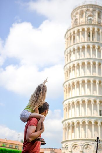 Family portrait background the Learning Tower. Pisa - travel to famous places in Europe.