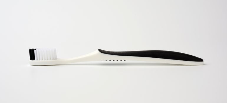 black plastic toothbrush for cleaning the oral cavity, object on a white background
