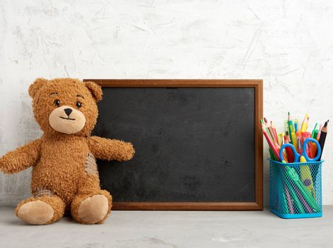 brown teddy bear and empty wooden rectangular frame, chalk board for writing a to-do list. Back to school