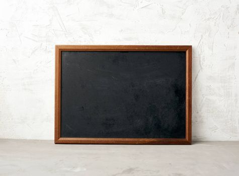 empty wooden rectangular frame, chalk board for writing a to-do list, menu on a white cement background. Back to school