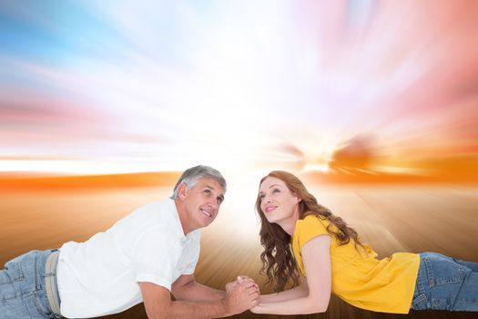 Casual couple lying and looking up against field with light wave