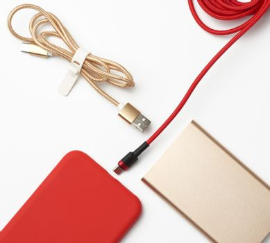 red smartphone and cable in textile braid on a white background