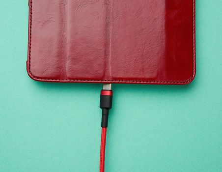 cable in red braid and electronic device on a green background