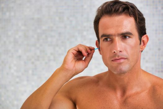 Man cleaning his ear with cotton bud