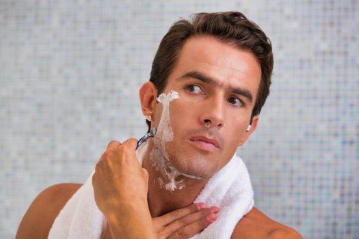 Handsome man shaving in bathroom