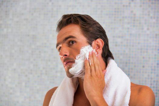 Portrait of attractive man applying beard foam in the bathroom
